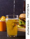 Small photo of Beer with burger and fries on dark wooden background. Ale and food, vertical