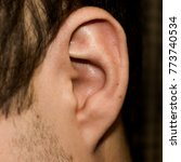 Small photo of Male ear. Adherent earlobe close-up. Square photo.
