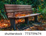 A Park Bench Sits In Under A...