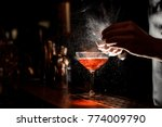 Stock photo barman s hands sprinkling the juice into the cocktail glass filled with alcoholic drink on the dark 774009790