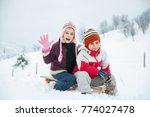 happy playful kid in snow | Shutterstock . vector #774027478