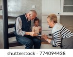 elderly couple showing a book... | Shutterstock . vector #774094438