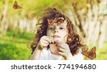 Stock photo curly girl looking at a butterfly on wild flower the child explores the nature 774194680