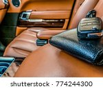 closeup of a black leather wallet and a car key kept on it inside an exotic vehicle with brown interior of the car in the background - stock photo