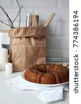 Small photo of Glazed pumpkin coffee bundt cake. Festive food on white background. Food styling. Close-up of Christmas decorated table with candles and kitchen stuff. Winter gathering. Baking idea for holidays