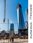 Small photo of NEW-YORK - NOV 9: Construction workers standing and talking from both sides of the fence with the WTC behind in New-York, USA on November 9, 2012.