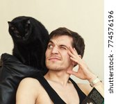 Stock photo black cat cuddles up to the man reading a book 774576196