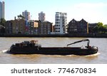 Small photo of Wapping, London, England - 09/10/15: Refuse barge on River Thames passing Rotherhithe, photographed from Captain Kidd pub.