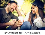 smiling young couple in park... | Shutterstock . vector #774682096