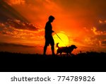 Stock photo silhouette of man and dog walking on sunset background 774789826