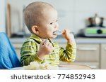the child in the kitchen eating ... | Shutterstock . vector #774852943
