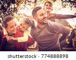 parents carrying little girls... | Shutterstock . vector #774888898