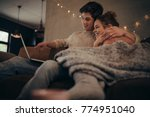 young couple sitting on sofa at ... | Shutterstock . vector #774951040