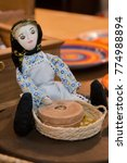 Small photo of Souvenir doll of a Portuguese character, lady with corn crushing stone.
