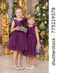 Small photo of Christmas Happy funny children child girl enjoying new year decoration studio with presents tree mirror and sofa chair dressed in casual airy dresses.