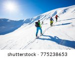 three skiers is climbing the... | Shutterstock . vector #775238653