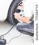 Small photo of man put on air pump jack to wheel for checking tire pressure , safety concept