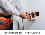 electrician at work on switches ... | Shutterstock . vector #775400446