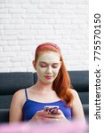 Small photo of Girl with beauty mask relaxing at home, messaging text on cell phone. Young woman texting message on smartphone, mobile telephone. Female beauty, skin and body care.
