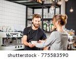 handsome barista giving a... | Shutterstock . vector #775583590