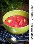 Small photo of Vegetarian red soup - borsch in green bowl on wooden background.