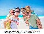 young family of four on beach... | Shutterstock . vector #775874770