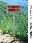 """Small photo of Kislovodsk, Stavropolsky Region, Russia - July 16, 2017: The white sign with red inscription in Russian """"Caution ahead abyss!"""" in the public park in Kislovodsk"""