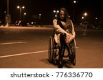 Small photo of Real people, disability and handicap. Teen handicapped girl in wheelchair stay on the night parking