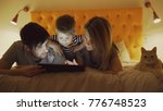 Stock photo happy family with little son and funny cat lying in bed at home and using tablet computer for 776748523