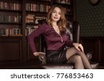 Small photo of Beautiful woman sits in a brown leather chair, personal assistant, secretary. Business image. Flirt, zigryat, put your foot on the foot.