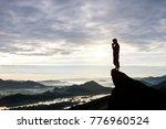 man praying on cliff against... | Shutterstock . vector #776960524