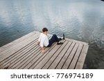 man near the water on a wooden...   Shutterstock . vector #776974189