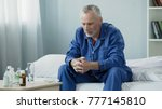 Small photo of Sad old man sitting in bed and looking at pills, medication and healthcare