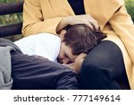 Small photo of Sad son comforting in mother's lap. Shy little boy hiding in mother's embrace.