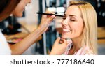 Small photo of Makeup artist applying liquid tonal foundation on the face of the woman in make up room