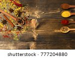 Small photo of Cuisine and flavouring concept. Set of spices on wooden background, copy space. Composition of condiment on sackcloth. Wood spoons with spices opposite to cinnamon, anise and scattered seasoning.