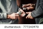 Small photo of Hand of addict man with money buying dose of cocaine or heroine or another narcotic from drug dealer. Drug abuse and traffic concept.