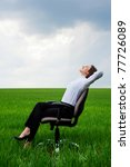 happy businesswoman resting on chair over green meadow - stock photo