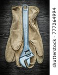 Small photo of Adjustable spanner safety gloves on wooden board.