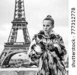 Small photo of Bold winter in Paris. modern fashion-monger in fur coat in the front of Eiffel tower in Paris, France looking into the distance