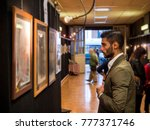 Stock photo side view of trendy confident man exploring art pieces in gallery 777371746