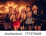 young women blowing confetti | Shutterstock . vector #777379600
