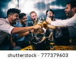 group of young men toasting at... | Shutterstock . vector #777379603