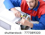 young repairman fixing and... | Shutterstock . vector #777389320