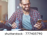 smiling man with smart phone at ... | Shutterstock . vector #777405790