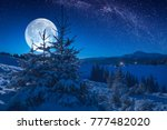 Majestic full moon rising above the carpathian mountain valley with small village on a hill covered with fresh snow. Fantastic milky way in a starry sky. Christmas winter night.