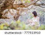 Small photo of asian short hair girl or woman sit and playing deflower flower on grass under tree. copy space for text