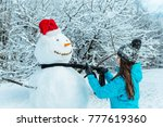 Woman Making Snowman In Winter...