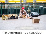 "Small photo of SYDNEY, AUSTRALIA. – On December 19, 2017. - Aboriginal Australian musician street shows playing ""Didgeridoo"" is a wind instrument developed by Indigenous people, performing at Circular Quay wharf."