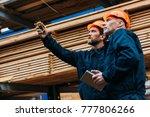 builders in helmets pointing... | Shutterstock . vector #777806266